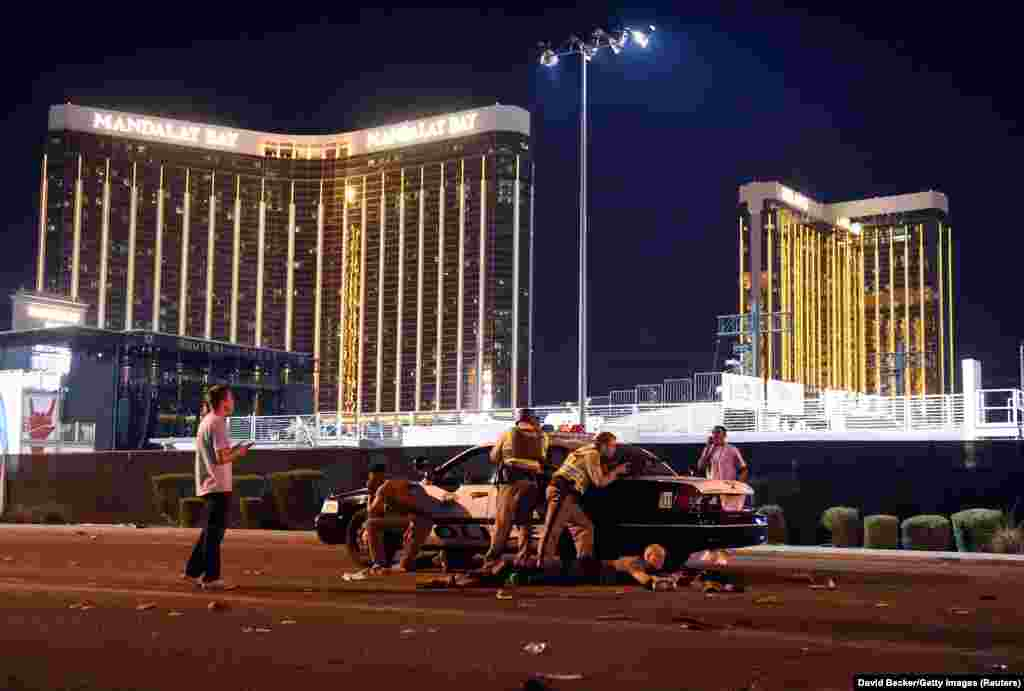 Police take cover outside the concert grounds after a gunman opened fire on concertgoers at the Route 91 country music festival in Las Vegas, Nevada, killing 58 and injuring more than 800. Spot News -- First Prize, Stories. (David Becker, Getty Images)