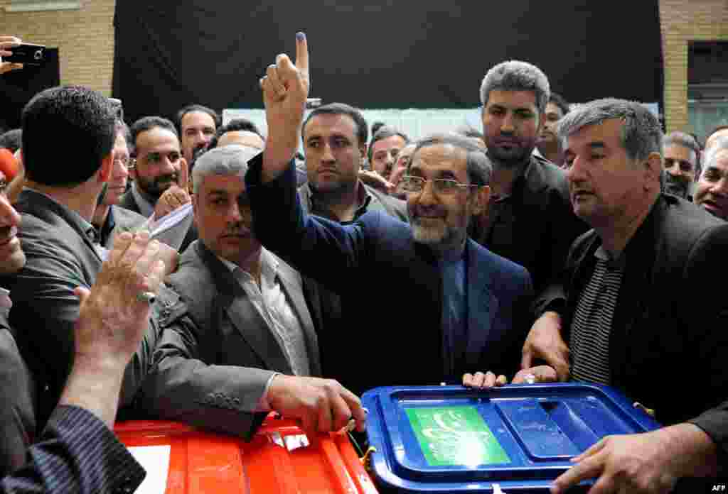 Presidential candidate Ali Akbar Velayati shows his ink-stained finger as he votes at a polling station in Tehran.