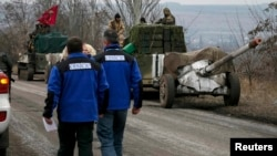Спостерігачі ОБСЄ біля колони з важким озброєнням українських сил, яке відводять від лінії зіткнення, 26 лютого 2015 року