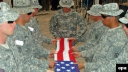 U.S. soldiers fold their national flag during a departure ceremony at Olsen camp in Samarra