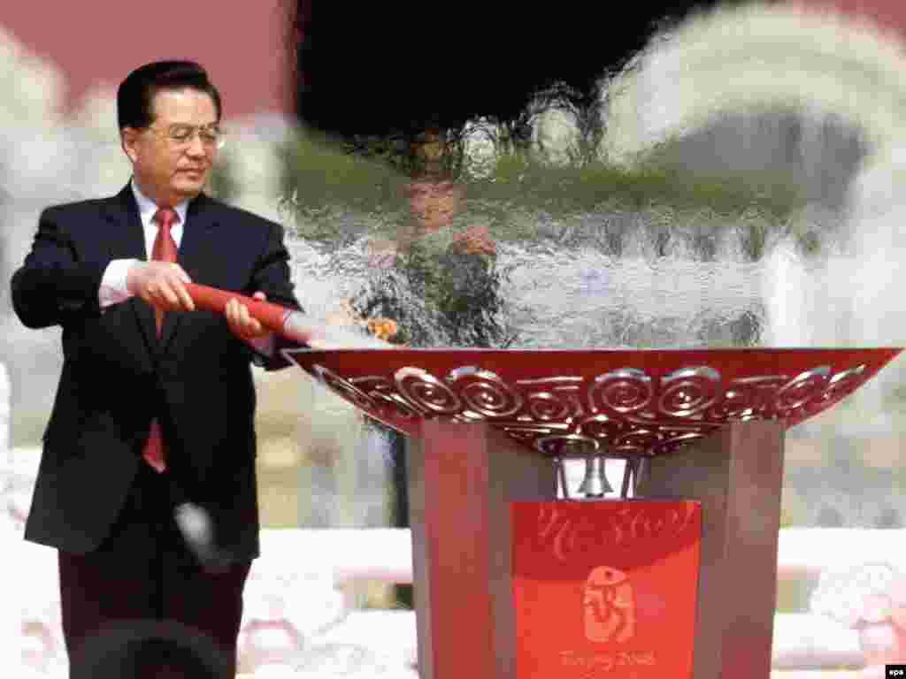Chinese President Hu Jintao lights the Olympic torch on Tiananmen Square in Beijing on March 31, 2008, ahead of a trip around the world that saw the flame travel 130,000 kilometers.