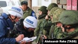 Сотрудники мониторинговой миссии ОБСЕ записывают серийные номера оружия сепаратистов, покидающих Золотое после начала разведения сил. 29 октября 2019 года.