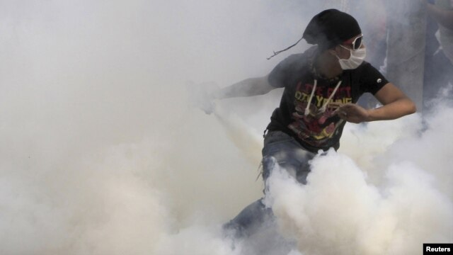 An antigovernment protester runs to throw a tear-gas canister back during clashes with Egyptian riot police on Tahrir Square in Cairo on November 27.