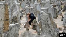Треблинка концлагерінде қаза тапқандарға тұрғызылған ескерткішке шырақ қойып жатқан бойжеткен. Польша, 2 қазан 2013 жыл. (Көрнекі сурет.)