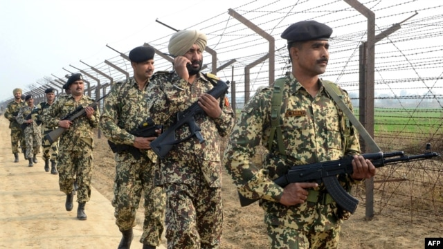Indian Border Security Force soldiers patrol along the India-Pakistan border fence.