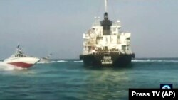 A photo provided by Iranian state TV showing the Panamanian-flagged oil tanker MT Riah surrounded by military vessels from Iran,