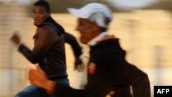 Туніські мігранти намагаються втікти з їхнього табору в Мандурії, Італія, 1 квітня 2011 року