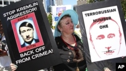 An anti-Russian protester holds placards at a rally during the G20 in Brisbane, Australia, in November 2014.