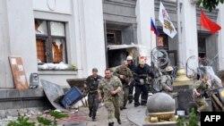 Орусиячыл согушчандар жана өрт өчүргүчтөр Луганск облбийлигинин имаратын таштап качууда. 2-июнь, 2014-ж.