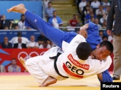Georgia's Lasha Shavdatuashvili fights with Japan's Masashi Ebinuma (in blue) during their men's 66-kilogram semifinal B judo match on July 29. Shavdatuashvili took home gold.