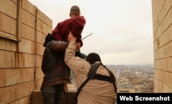 Islamic State militants prepare to throw a man from a high rooftop as punishment for allegedly being gay in Mosul.