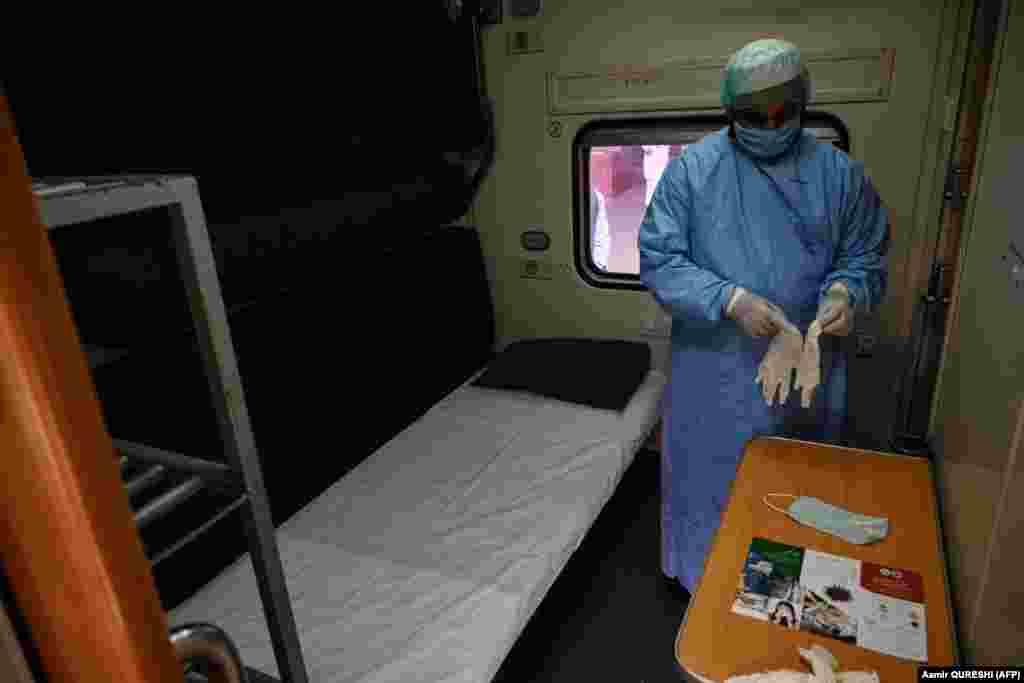Медицинский работник в защитном костюме надевает перчатки в вагоне поезда, который используется в качестве временного изолятора в Равалпинди, Пакистан.