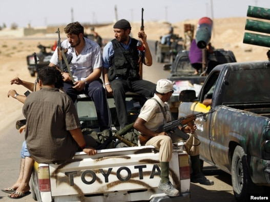Rebel fighters patrol the town of Abu Grein, some 128 kilometers west of Sirte, on August 29.