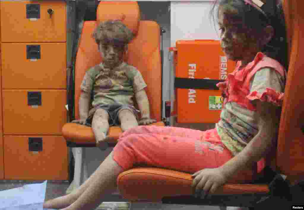 Five-year-old Omran Daqneesh, bewildered, covered in dust and with a bloodied face, sits with his sister inside an ambulance after they were rescued following an air strike in the rebel-held Al-Qaterji neighborhood of Aleppo, Syria. He and his sister were not seriously wounded, but officials said Omran's brother, Ali, who was 10, died from injuries suffered in the same attack. Images of Omran were widely circulated on social media and drew further attention to the plight of civilians in Syria's ongoing civil war. (Reuters/Mahmoud Rslan)
