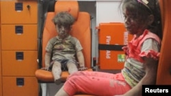Five-year-old Omran Daqneesh, with bloodied face, sits with his sister inside an ambulance following an air strike in Aleppo.