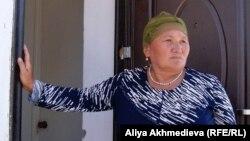 Жительница села Кызылагаш Алтынхан Карпаева стоит на пороге своего нового дома. Август 2010 года.