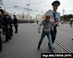 A young boy is led away by police in St. Petersburg on September 9.