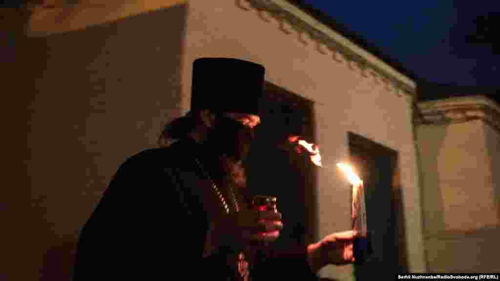 Благодатний вогонь священники роздавали людям. Намісник Воскресенської церкви Сергій Ющик несе вогонь до людей