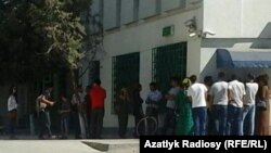 People wait to withdraw cash from an ATM machine in Ashgabat.