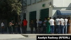 People wait to withdraw cash from ATM machines in Ashgabat.