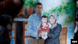 18 aýlyk Ali Dawabşa (ortada) öz kakasy Saad (ç) we ejesi Riham (s) bilen, 31-nji iýul, 2015