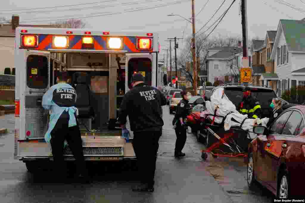 Medics and firefighters bring a patient to the ambulance amid the coronavirus disease (COVID-19) outbreak in Revere, Massachusetts, U.S.
