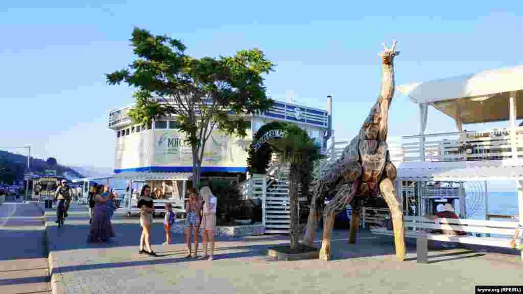 Инсталляция жирафа привлекает внимание отдыхающих. Здесь останавливаются, чтобы сделать фото на память