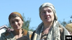 Ingush women hold photos of kidnapped relatives