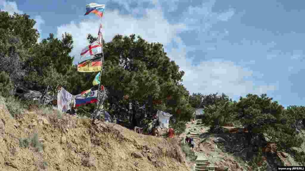 У пляжа– палаточный лагерь любителей единения с природой, на импровизированном флагштоке– флаги разных государств, среди них и украинский
