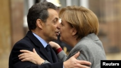 "Fraench President Nicolas Sarkozy (left) and German Chancellor Angela Merkel have been working so closely in recent weeks that commentators have taken to calling them ""Merkozy."""