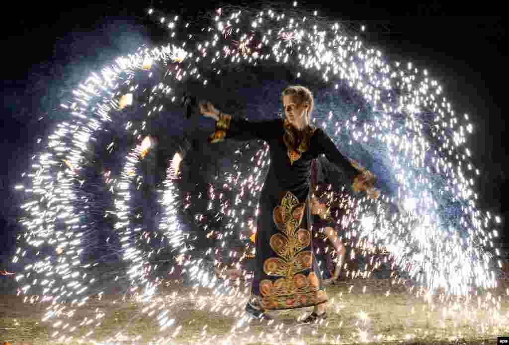 A woman performs a fire show at the Cucuteni International Festival near the village of Ivancea, north of Chisinau, Moldova. The Cucuteni festival is an arts event dedicated to the preservation of the traditional arts, as well as the promotion of local brands and artisans. (epa/Dumitru Doru)