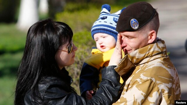 A Ukrainian marine speaks with family members before departing Crimea outside a Ukrainian military base in the Crimean port city of Feodosiya on March 24.