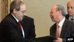 نائب وزير الخارجية السوري فيصل المقداد (يسار) يصافح نائب أمين عام جامعة الدول العربية أحمد بن حلي في القاهرة.