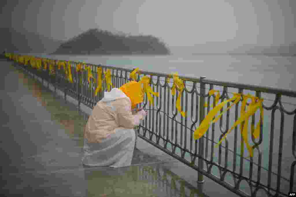 "A relative of one of the hundreds of victims of the ""Sewol"" ferry disaster weeps in front of yellow ribbons at South Korea's Jindo harbor. Three hundred and two people were still dead or still missing on April 26, the majority of them schoolchildren, while 174 people survived, including 22 of 29 crew members. (AFP/Ed Jones)"