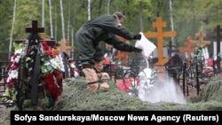 A man wearing protective gear pours a white substance into a grave during a funeral at a cemetery amid the outbreak of the coronavirus disease in Moscow on May 26.