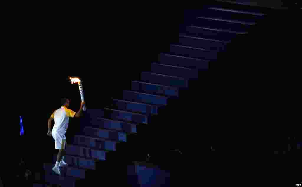 Former Brazilian marathon runner Vanderlei de Lima climbs the stairs to light the Olympic flame.