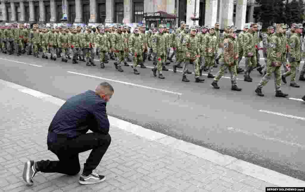Чоловік став на коліно перед учасниками Маршу пам'яті полеглих захисників України у війні з Росією на Донбасі. Київ, Хрещатик, 8 травня 2019 року