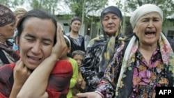 Қырғызстанның Ош қаласы маңындағы босқындар лагеріндегі этникалық өзбек әйелдері жәрдем сұрап жылап тұр. 15 маусым 2010 жыл.