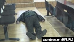 Armenia - Activist Vargdes Gaspari lies down in a courtroom during his trial, Yerevan, 21Jan2016.