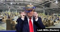 Президент США Дональд Трамп тримає захисний щит проти коронавірусу під час візиту на завод Ford Rawsonville Components, який виробляє вентилятори штучного дихання, захисні маски і щити та інше спорядження проти коронавірусу
