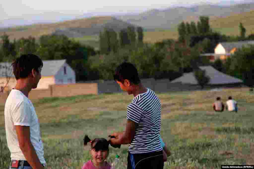 Ауыл шетіндегі трасса бойында ойнап жүрген кішкентай қыздардың бірі ағасына келіп шашын жинатып жатыр.