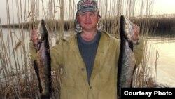 Мужчина показывает хищную рыбу, пойманную им в озере Балхаш.