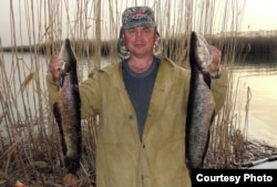 Павел Шархун гарпунмен атып алынған жыланбас балықтарды көрсетіп тұр. 2012 жылдың сәуірі. Фото жеке архивтен алынды.