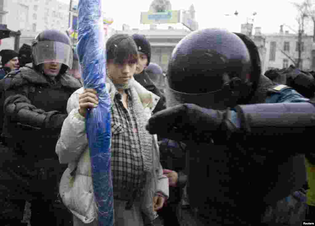 Riot police detain a pregnant Nadezhda Tolokonnikova (center) during a dissenters' march in Moscow in March 2008.