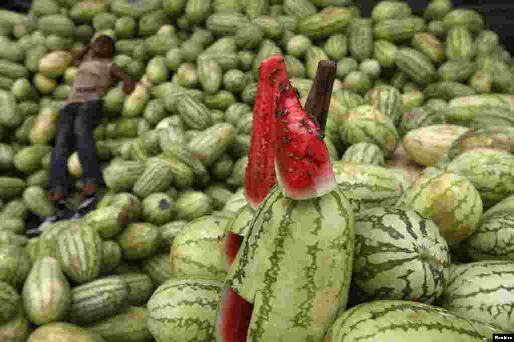 A roadside fruit vendor takes a nap at his makeshift stall as bees crawl on a slice of watermelon on display in Karachi, Pakistan. (Reuters/Athar Hussain)