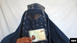 An Afghan woman shows her voter registration card.