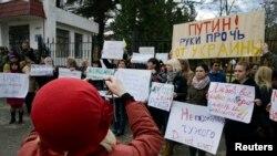 """Симферопол шаарында өткөрүлгөн согушка каршы пикетти бир айым сүрөткө тартууда. Плакаттардын биринде """"Путин, Украинадан колуңду тарт!"""" деп жазылган. Крым, Украина, 05.3.2014."""