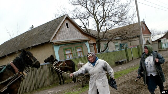 Local women walk on a muddy road in the village of Chirsova, in the autonomous region of Gagauzia. (file photo)