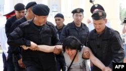 Kazakh police officers detain an opposition supporter attempting to stage a protest rally in Almaty on June 23.