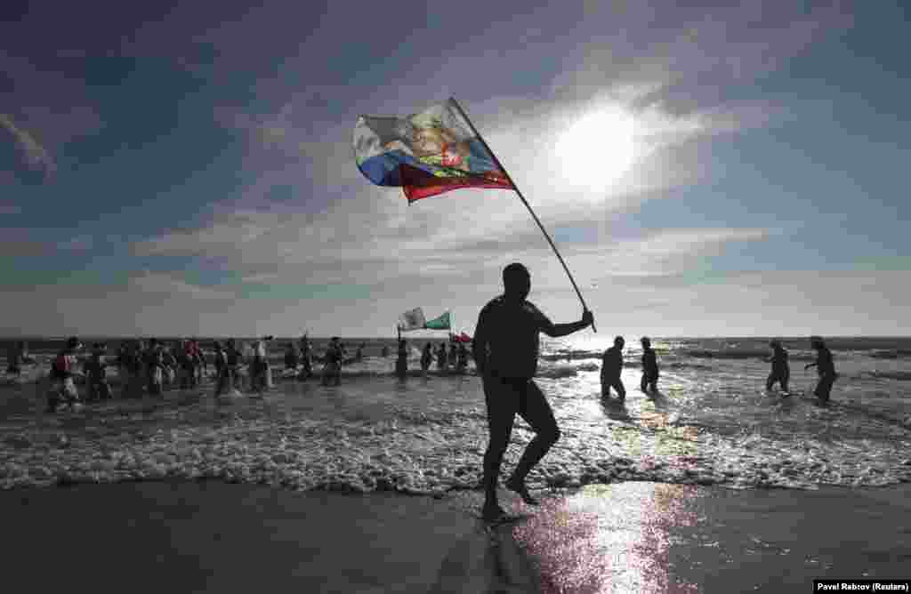 Қырымдағы Рождество мерекесі кезіндегі қысқы жүзу шарасында Ресей туын ұстап жүрген ер адам.